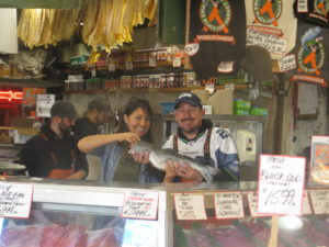 Pam poses with salmon and Chris Bell, Pike Place Market fishmonger.