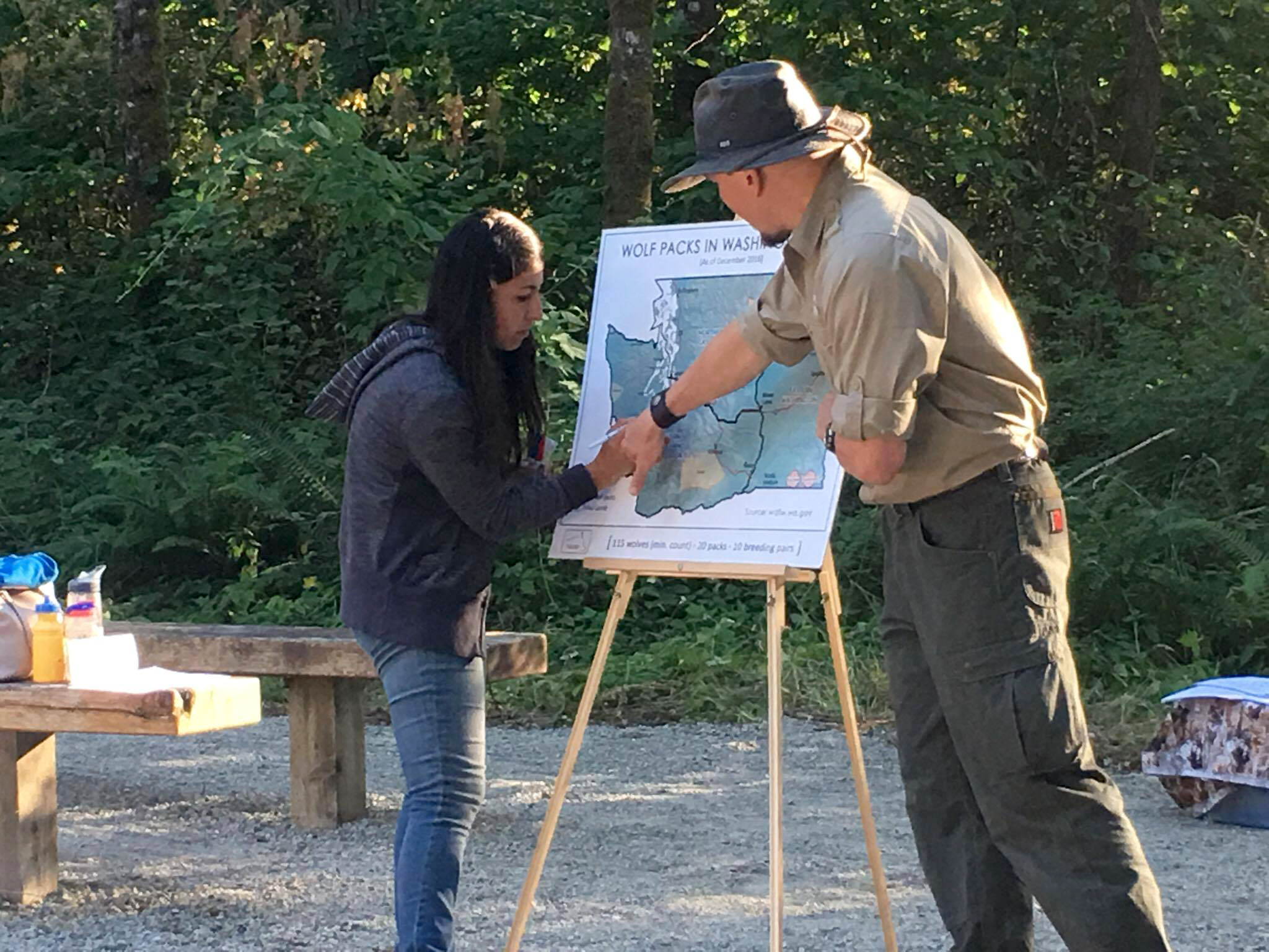 Pamela Maciel and Chris Montera of Wolf Haven with a map of Washington that displays where wolf packs reside. in the state